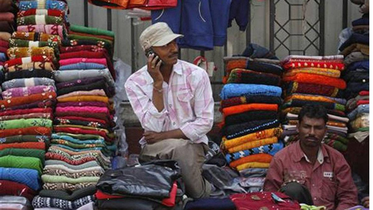 A vendor speaks on his mobile phone as he waits for customers at his roadside shop selling clothes in Mumbai February 2, 2012.