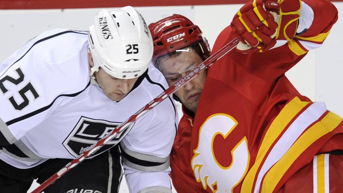 Los Angeles Kings' Dustin Penner, left, collides with Calgary Flames' Cory Sarich during second period NHL action, in Calgary, Alta., Saturday, Jan. 14, 2012. THE CANADIAN PRESS/Larry MacDougal