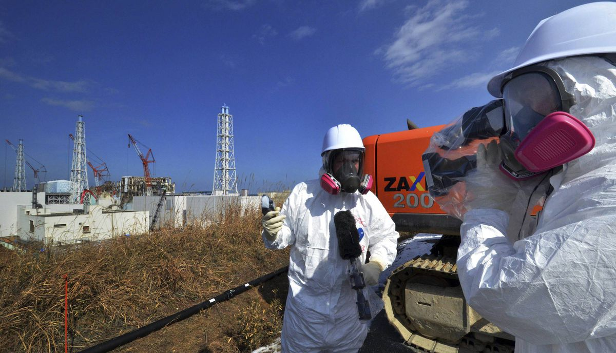 A video journalist checks the radiation level with her dosimeter near the crippled Tokyo Electric Power Co. Fukushima Daiichi nuclear power plant reactor buildings in Fukushima prefecture February 28, 2012.