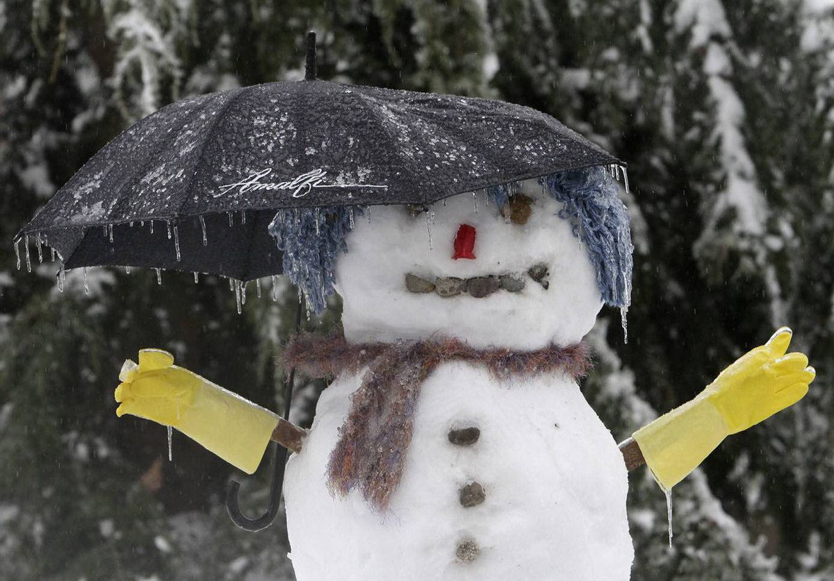A snowman with an umbrella is covered in ice in a Renton, Washington neighborhood.