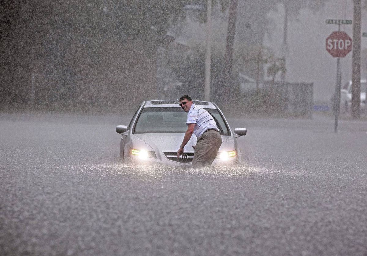 James Pyle, of West Palm Beach, tries to push his car after it stalled during heavy afternoon rains in West Palm Beach, Fla.