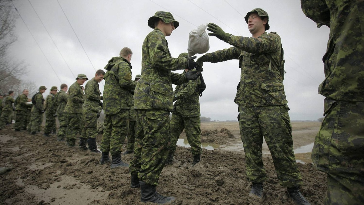 Military personnel from the C Company, 2PPCLI, help sandbag just outside Poplar Point in Manitoba, Monday, May 9, 2011. The high water levels of the Assiniboine River are threatening surrounding communities.