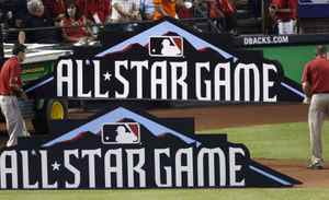 Workers prepare signs for the field prior to Major League Baseball's All-Star Game in Phoenix, Arizona July 12, 2011.
