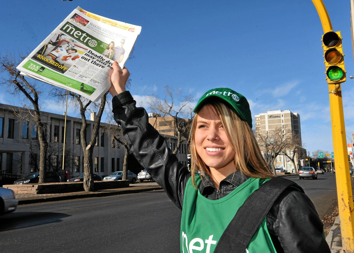 Promoter Brittany Bartel holds up a copy of a Metro newspaper in downtown Regina. The commuter daily will begin free daily distribution in Regina and Saskatoon on Monday.