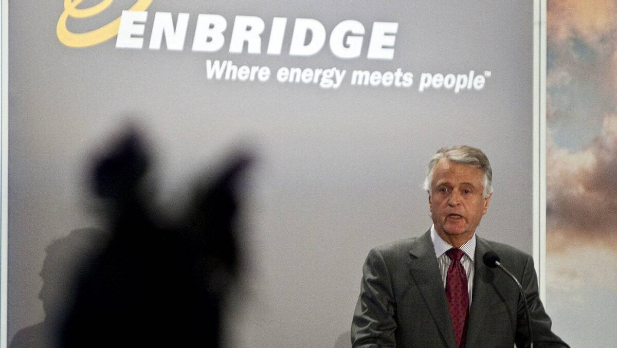 Patrick Daniel, president and CEO of Enbridge, addresses the company's annual meeting as Tsohdih Erickson, hereditary chief of the Beaver Clan, from Fort St, James, B.C., wearing a native headdress looks on in Calgary, Wednesday, May 11, 2011