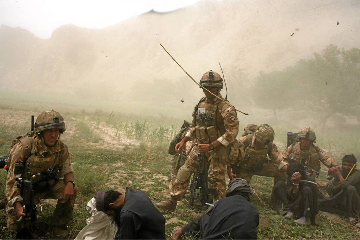British paratroopers from the 3rd Battalion Parachute Regiment stand with detainees before boarding a Chinook helicopter to return to their base in the village of Segera, Kandahar, in 2008. The regiment had conducted a joint operation with U.S. and Afghan forces to capture Taliban leaders. Eight Taliban were captured and detained.
