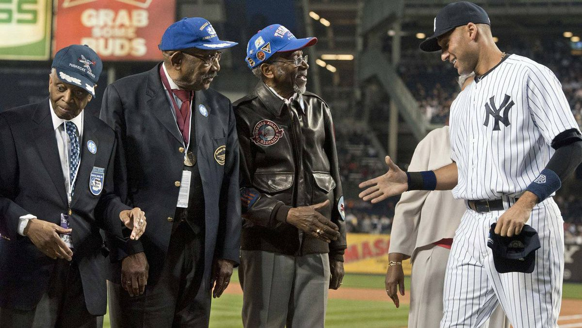 New York Yankees shortstop Derek Jeter (R) reaches to shake hands with World War II surviving Tuskegee Airmen Wilfred Defour (R-C), Dabney Montgomery and Reginald Brewster (L) as they were honored before their MLB American League baseball game with the Los Angeles Angels at Yankee Stadium in New York, April 15, 2012. The Yankees won 11-5. REUTERS/Ray Stubblebine