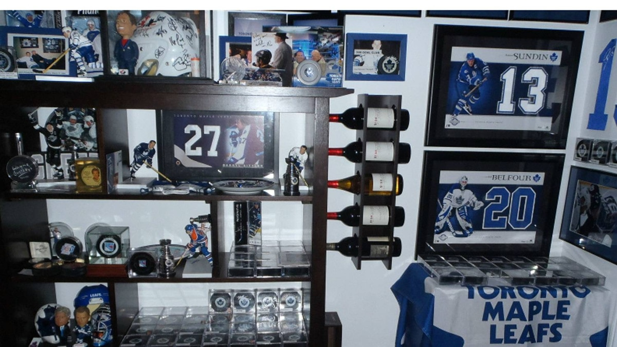 Another wall of the sports memorabilia room that includes a hockey helmet signed by all of Team Canada on winnning a gold medal. Other notables: bottles of wine from Wayne Gretzky's winery, a Gretzky bobblehead, autographed photos and pucks