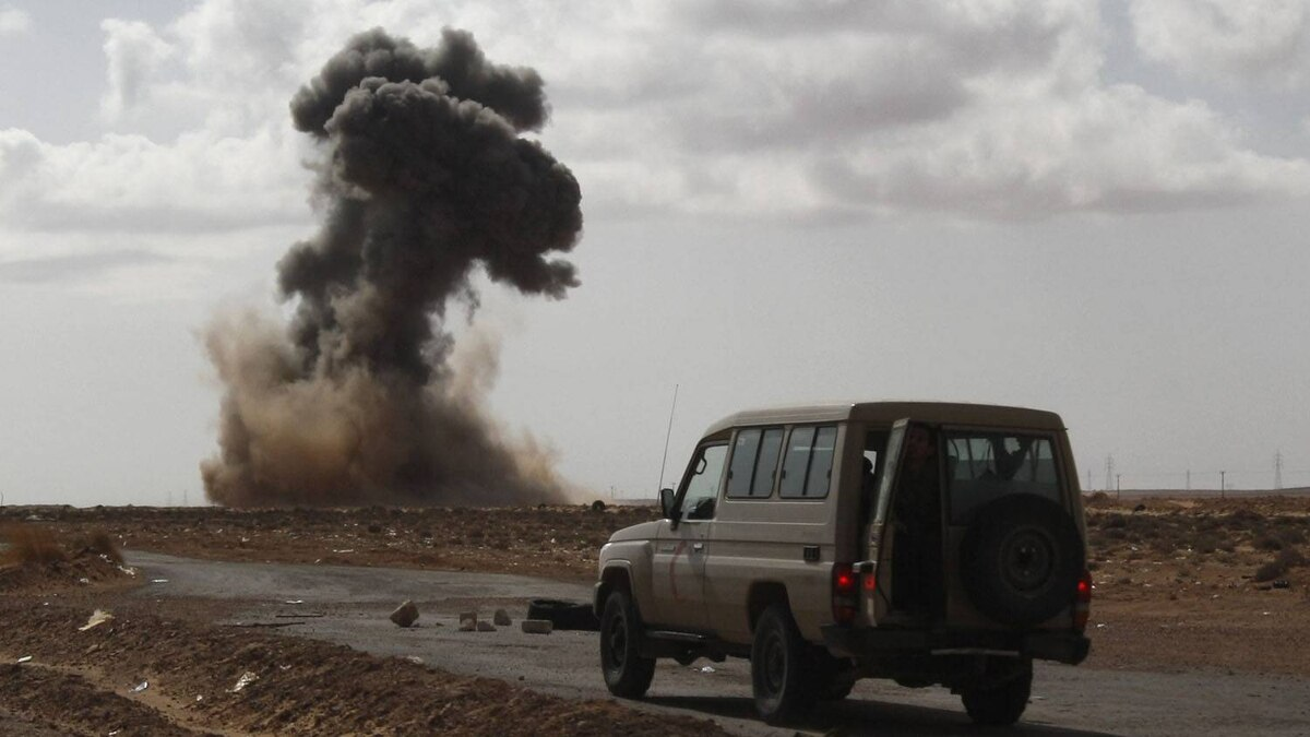 Anti-Gadhafi rebels drive a vehicle forward as smoke rises following an air strike by pro-Libyan leader Moammar Gadhafi warplanes that attacked a highway leading to the town of Ras Lanouf, eastern Libya, Tuesday, March 8, 2011. Libyan warplanes launched at least three new airstrikes Tuesday near rebel positions in the oil port of Ras Lanouf, keeping up a counteroffensive to prevent the opposition from advancing toward leader Moammar Gadhafi's stronghold in the capital Tripoli.