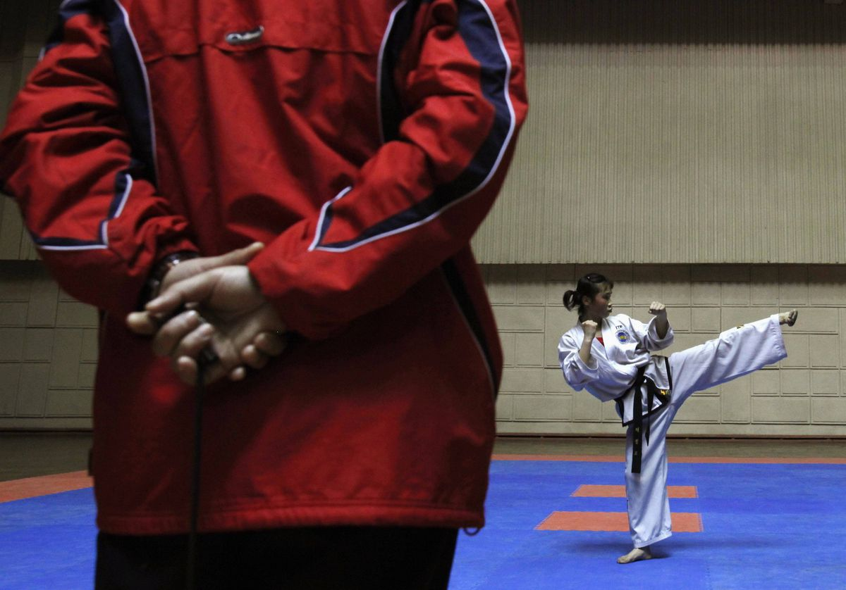 A girl receives training in front of her coach in a taekwondo hall in Pyongyan. Students trained here are selected from different provinces, with some presenting North Korea to compete in international taekwondo competitons.
