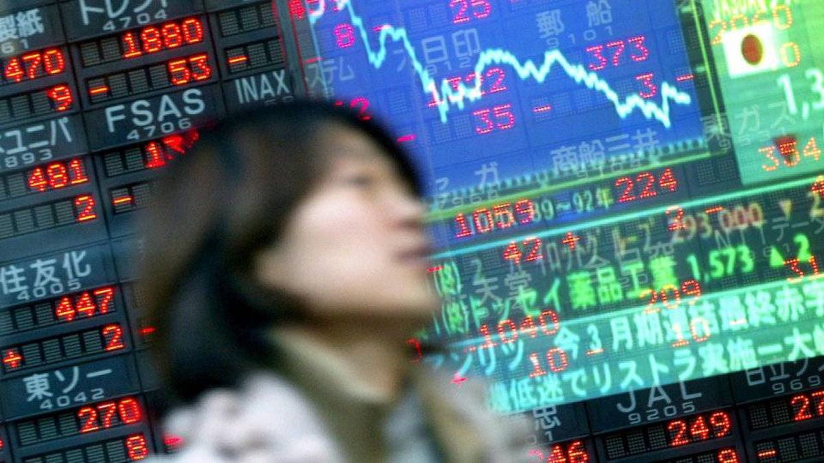 A woman passes in front of an electronic share price board displayed in the window of a stock brokerage in downtown Tokyo.