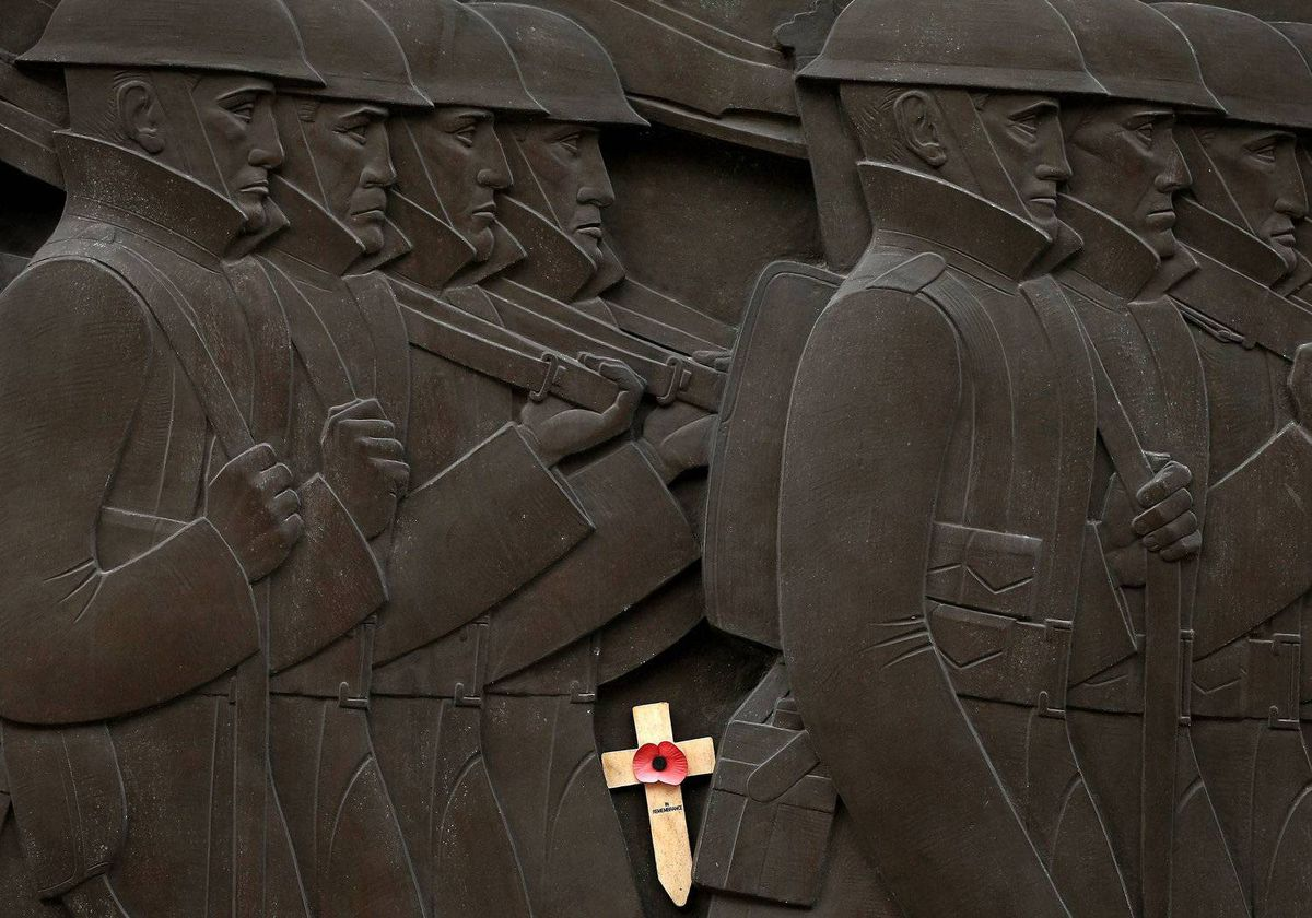 A remembrance day cross with a poppy on it is wedged between carvings of soldiers on the cenotaph in Liverpool, northern England, April 22, 2012.