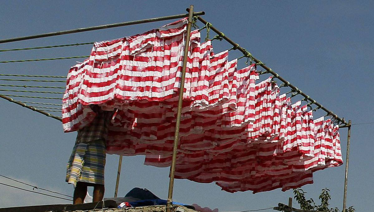 A laundryman hangs washed clothes out to dry at the Dhobi Ghat open air laundry in Mumbai.