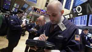 Damian Bagarozza, right, works with fellow traders on the floor of the New York Stock Exchange Monday, March 19, 2012.