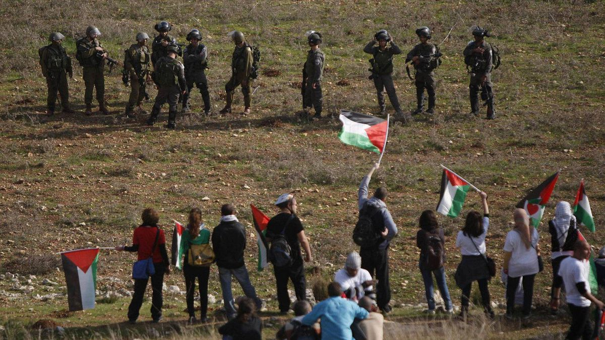 Palestinians demonstrate against the expansion of the nearby Jewish settlement of Halamish as Israeli forces stand by in the West Bank village of Nabi Saleh near Ramallah, Friday, Dec. 16, 2011.
