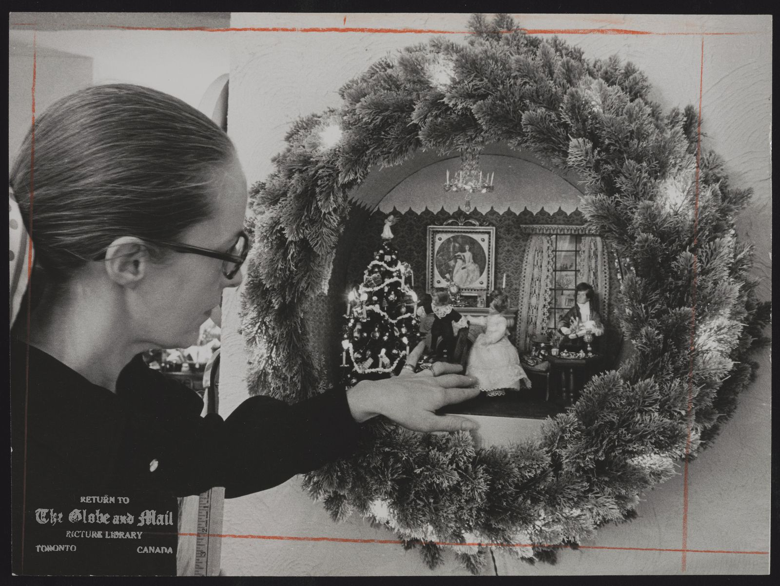 CHRISTMAS DECORATIONS Patricia Mumford shows miniature wreath depicting a Victorian Christmas in Old Oakviile, about 1850, Scale is one inch to a foot. The tree lights are the size of 8.grain of wheat. The Mumfords are leaving the wreath as a gift to to the township of Oakville.