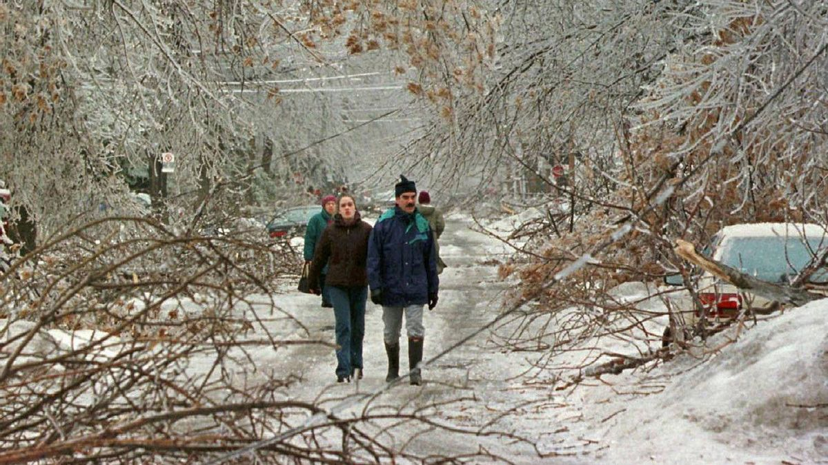 Pedestrians make their way past downed trees as an ice storm ripped through Montreal in this Jan. 6, 1998 photo. The ice storm left parts of Quebec and Ontario without electricity for days as ice-covered trees crashed down on power lines.