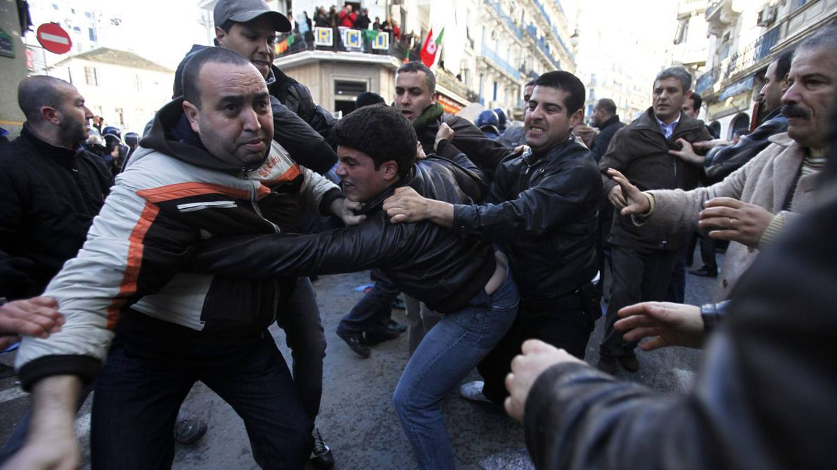 Policemen detain a protester (C) during a demonstration in downtown Algiers January 22, 2011. A small group of Algerian opposition supporters trying to hold a banned protest clashed with police in the capital and several people were injured, protest organisers and official media said on Saturday.
