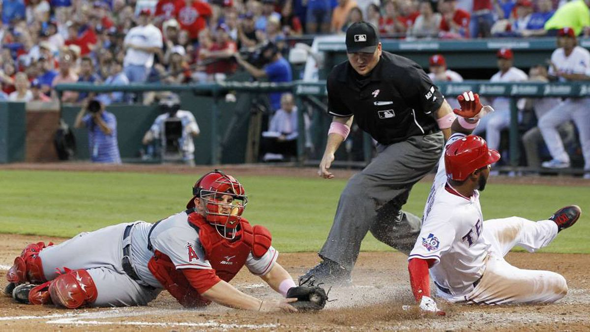 Texas Rangers' Elvis Andrus slides safely into home plate as Los Angeles Angels catcher Bobby Wilson cannot make the tag in time in the third inning of their MLB American League baseball game in Arlington, Tex.
