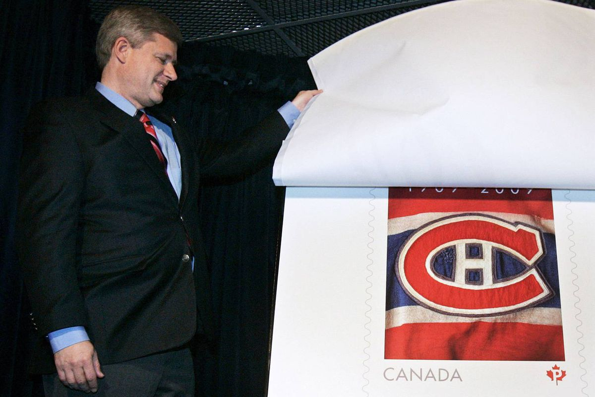 Prime Minister Stephen Harper unveils a new postage stamp honouring the Montreal Canadiens centennial during an NHL hockey pre-game ceremony in Montreal on Oct. 17.