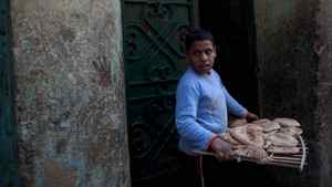 A young boy carries a tray of pita bread as he passes the painted hamsas that decorate the entrance of his home in Cairo's Sayeda Zeinab neighbourhood on November 24, 2011. The hamsa, depicted by an open right hand, is a symbol popular throughout the Middle East and North Africa and provides defence against the evil eye. The image has been recognized and used as a sign of protection in many societies throughout history. It is also known as the hand of Fatima, named for Muhammad's daughter Fatima Zahra.