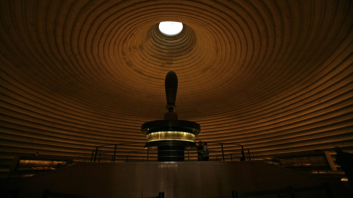 Visitors look at a facsimile of the Isaiah Scroll, one of the Dead Sea Scrolls, displayed inside the Shrine of the Book at the Israel Museum in Jerusalem September 26, 2011.