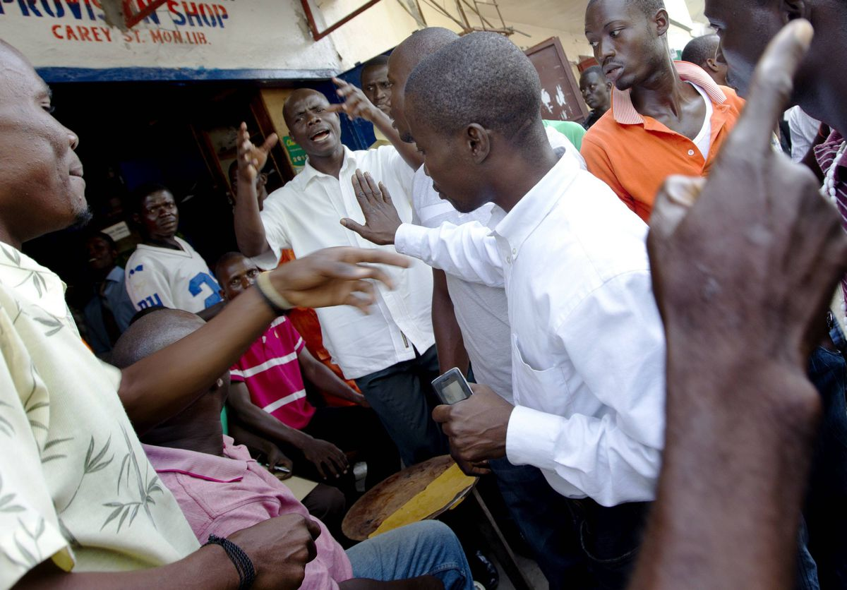 A group of men have a heated discussion in downtown Monrovia, Liberia about the guilty verdict against former President Charles Taylor.