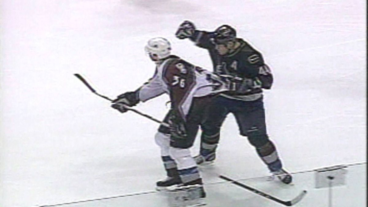 First in series of video frame grabs showing Vancouver Canucks Todd Bertuzzi (right, dark jersey) about to hit Colorado Avalanche player Steve Moore durign an NHL game at Vancouver Monday, March 8, 2004.