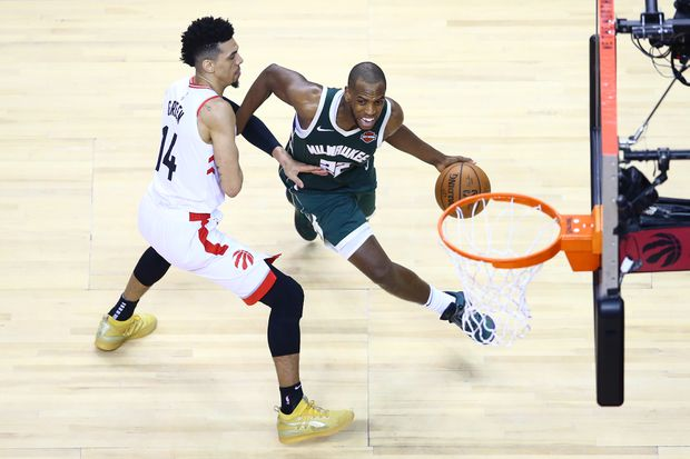 a19ca582c7b Khris Middleton (22) of the Milwaukee Bucks drives to the basket against Danny  Green (14) of the Toronto Raptors during game three of the NBA Eastern ...