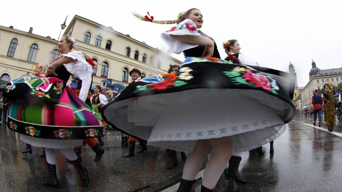 People in traditional costumes dance during the Oktoberfest parade in Munich September 18, 2011.