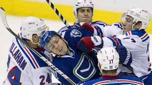 Vancouver Canucks right wing Alex Burrows (14) gets pushed around by New York Rangers right wing Ryan Callahan (24), Dan Girardi (5), Ryan McDonagh (27) and New York Rangers left wing Brandon Dubinsky (17) during second period NHL hockey action at Rogers Arena in Vancouver, B.C. Tuesday, Oct.18, 2011. THE CANADIAN PRESS/Jonathan Hayward