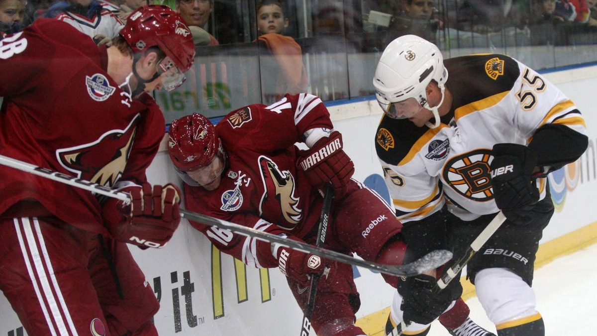 Lauri Korpikoski, left, and Taylor Pyatt, center, both of Phoenix Coyotes fight for a puck with Johnny Boychuk, right, of Boston Bruins during their NHL hockey match in Prague, Czech Republic, Sunday, Oct. 10, 2010.