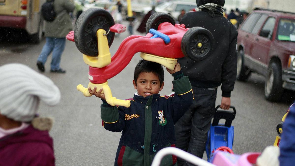 A boy carries a tricycle he received during an annual gift-giving event organised by firefighters in Ciudad Juarez December 24, 2011. The firefighters from Ciudad Juarez collect donated toys throughout the year for Christmas and hand them out to poor children on Christmas eve. Picture taken December 24, 2011.