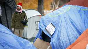 A protester watches police and bylaw officers hand out eviction notices to Occupy Calgary protesters in Calgary, Alta., Tuesday, Nov. 15, 2011. Occupiers of the small tent city were given 24 hours to leave.