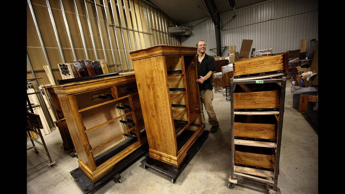 A Vokes Furniture employee moves nearly finished furniture from the lacquer spraying area at the Shallow Lake factory.