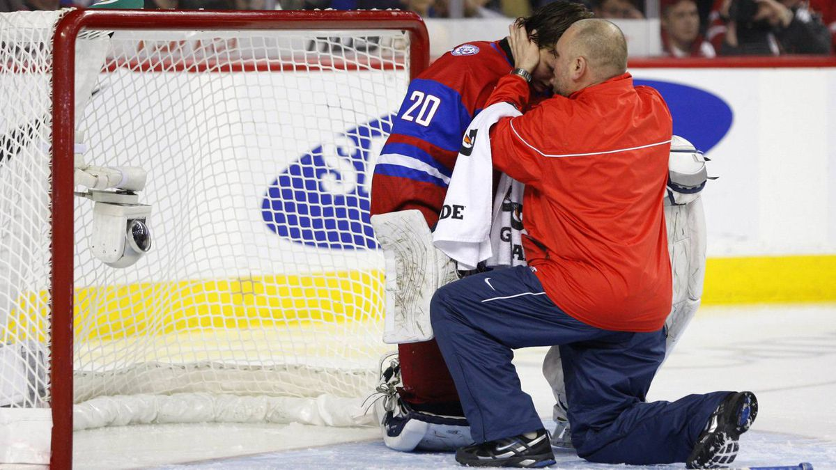 Russia goalie Andrei Makarov is checked out by a team medic after being hit by Sweden's Rickard Rakell during the third period.