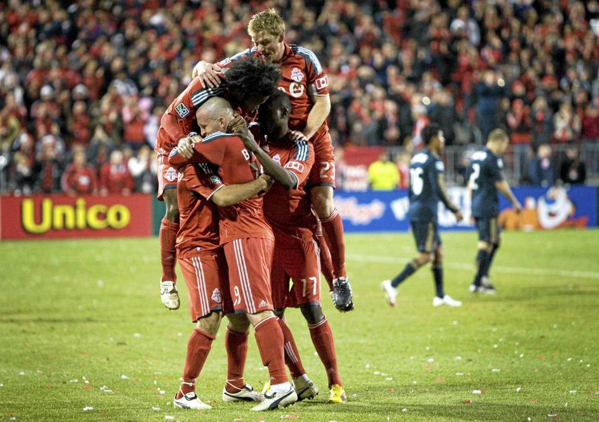 Toronto FC players celebrate the game-winning goal by Dwayne De Rosario last night at BMO Field. TFC topped Philadelphia 2-1 in their 2010 season home opener. Photo by Peter Power / The Globe and Mail