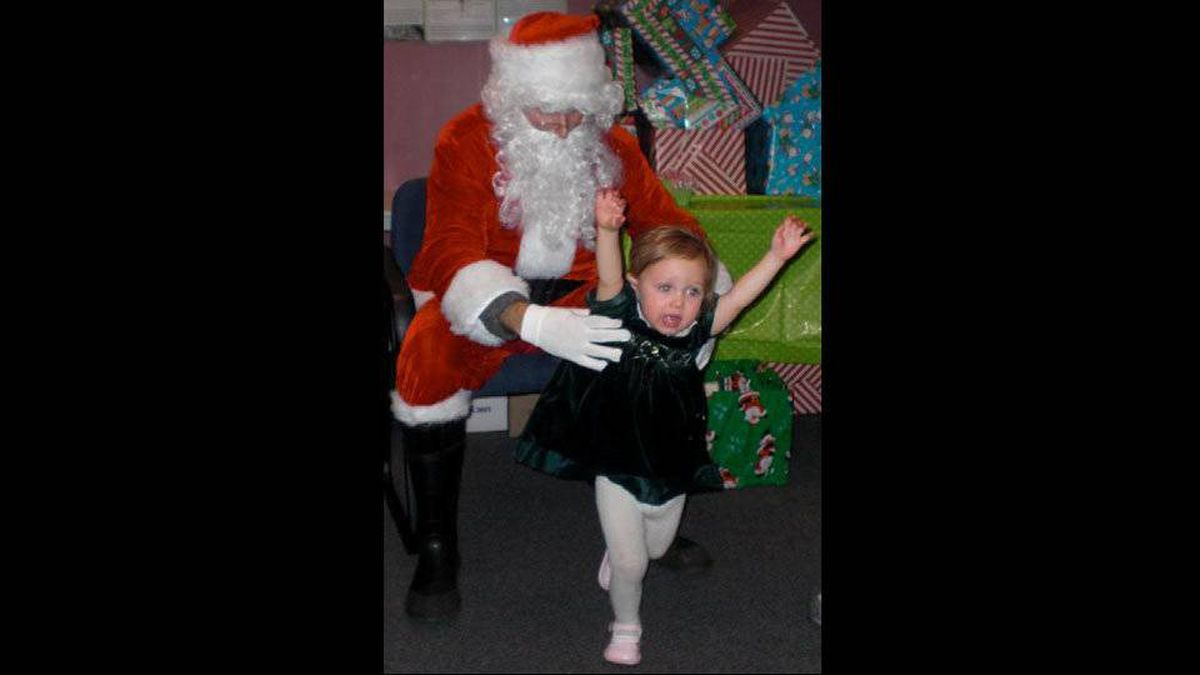 Barbara Sochanski writes: Evelyn's first meeting with Santa Claus. Our 19 months old daughter very clearly and loudly indicated she didn't want to be anywhere close to this scary man. She squirmed her way out of his grip and ran away as fast as she could.