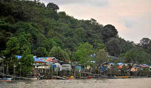 Colourful shanties on stilts back onto the forest in this Malaysian fishing village.