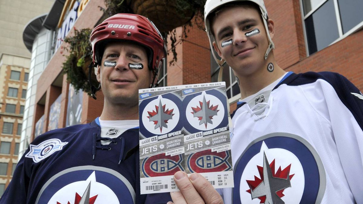 Winnipeg Jets fans Nelson (R) and Doug Quara show off their tickets before the NHL Winnipeg Jets inaugural game against the Montreal Canadiens in Winnipeg, October 9, 2011. REUTERS/Fred Greenslade
