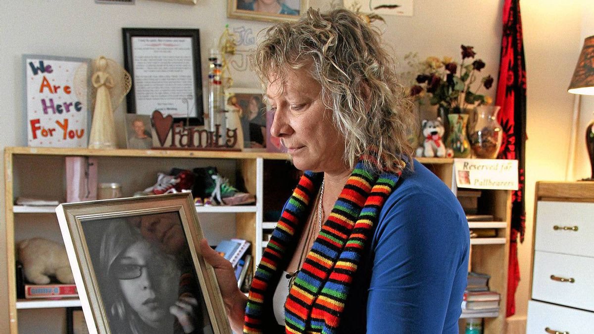 Donna Leslie looks a her daughter Loren's photo at her home in Vanderhoof. Leslie sits on a casket made for Loren, was signed by her friends in the comminity. Loren was cremated and here ashes are kept in Loren's Eeyore pillow bag.