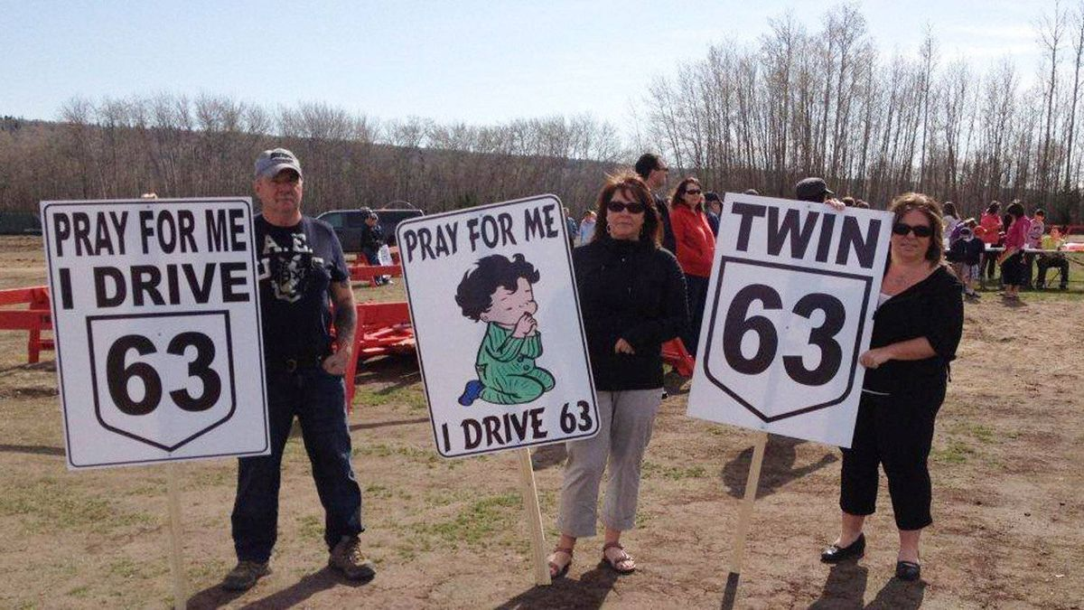 Protesters hold signs at a rally in Fort McMurray, Alta. Saturday, May 5, 2012. Organizers say almost 2,000 people rallied to push the Alberta government to quickly finish twinning a dangerous highway that was the scene of a horrific crash. Seven people died in the crash on Highway 63, the main route between Edmonton and the oilsands capital of Fort McMurray.