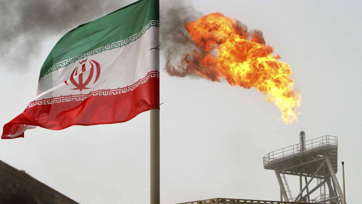 Gas flares from an oil production platform, as an Iranian flag is seen in the foreground, at the Soroush oil fields in the Persian Gulf, some 1,250 km south of the capital Tehran in this July 25, 2005 file photo.