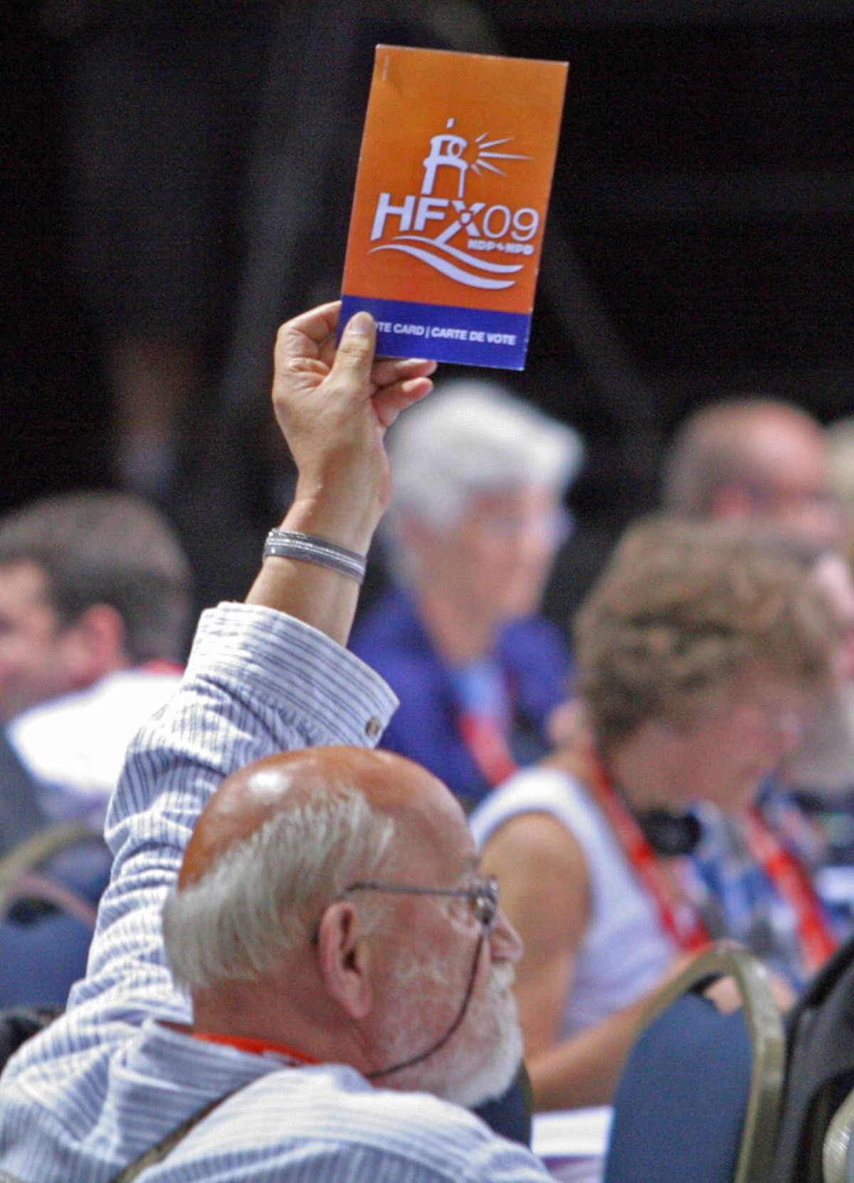 A delegate votes on a procedural motion during the opening session of the NDP national convention in Halifax.