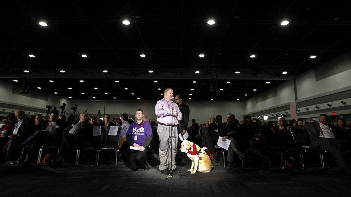 Dog guide Boone sits obediently by his master, Bob Brown, of Brantford, who is visually impaired, during a delay in voting on day two of the Liberal Convention. There was a debate over the reading of each recommendation to accommodate those who had trouble reading them on the screen.