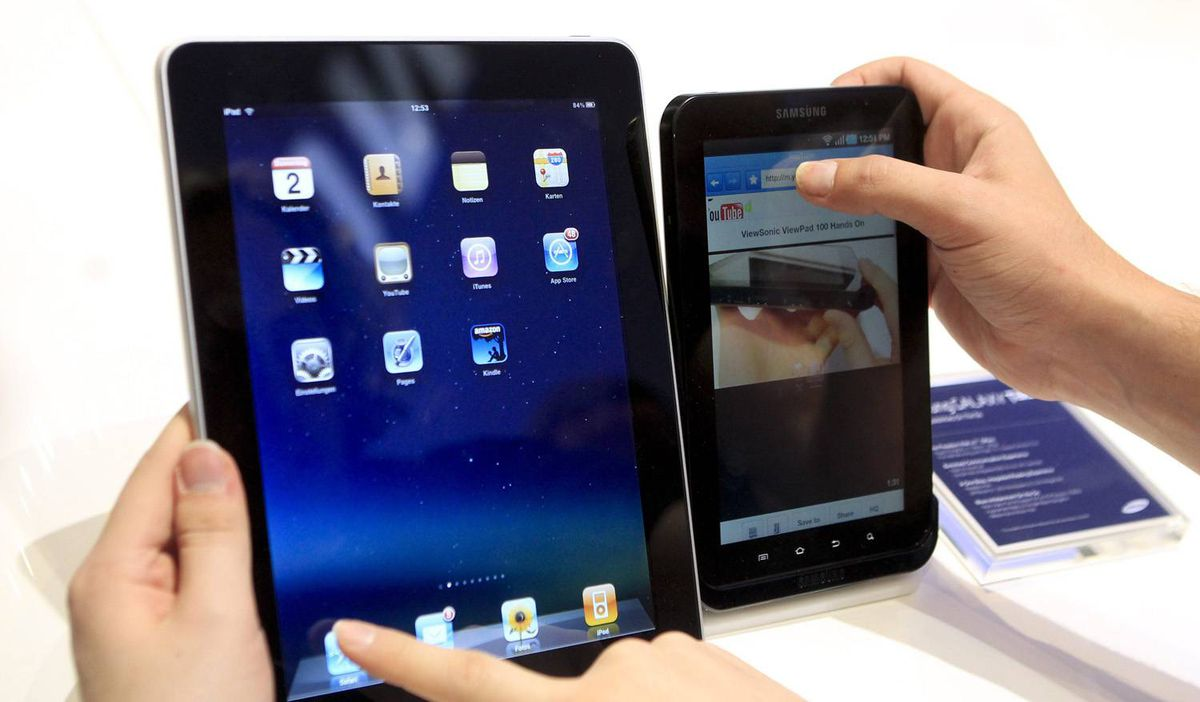 """People compare the performance of Apple's iPad (L) and Samsung's Galaxy Tab tablet devices at the Internationale Funkausstellung (IFA) consumer electronics fair at """"Messe Berlin"""" exhibition centre in Berlin, September 2, 2010."""