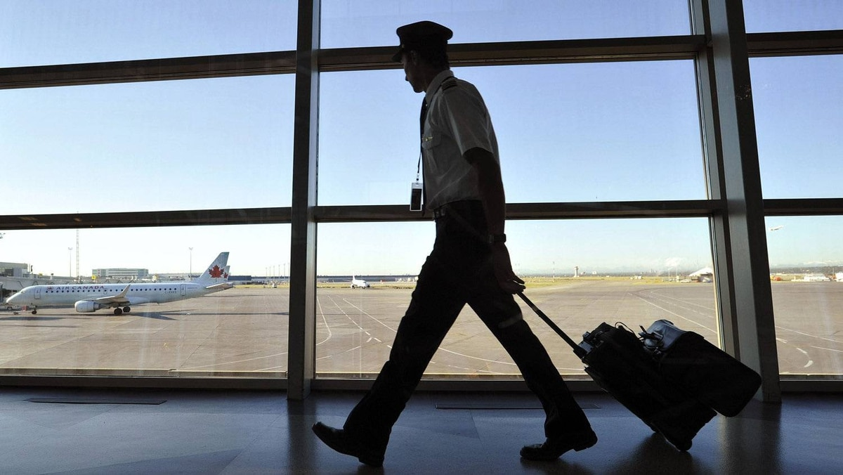 An Air Canada pilot walks to his plane at the International airport in Calgary. If the Air Canada Pilots Association were to obtain a strike mandate, the union has to provide 72-hour notice of any walkout.