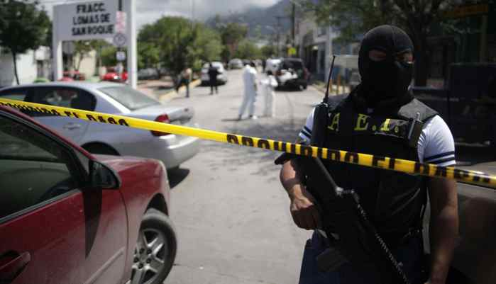 A federal police officer stands behind a police line at a crime scene in the municipality of Guadalupe in Monterrey April 10, 2012. Gunmen on Tuesday shot dead seven taxi drivers on the outskirts of the industrial hub of Monterrey, which has become one of Mexico's most violent cities during a turf war between rival drug cartels. The taxi drivers were killed as they waited at two depots next to their Volkswagen Beatle cars in Guadalupe, six kilometres from Monterrey's center.