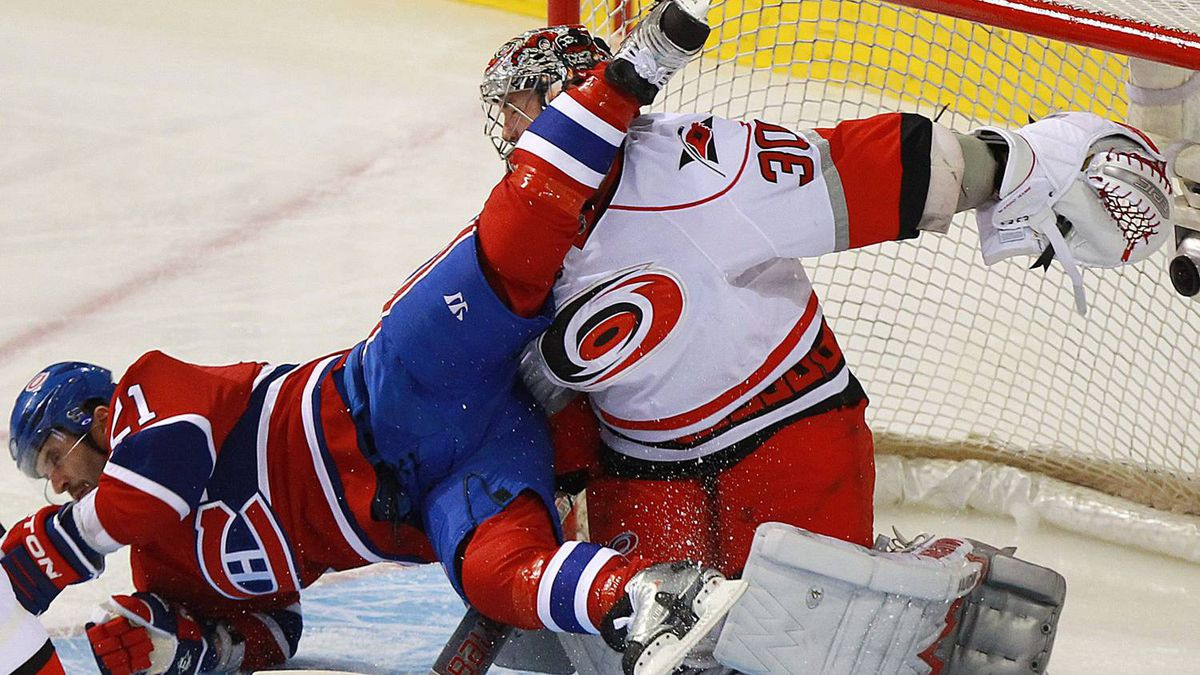 Montreal Canadiens Brian Gionta (21) is upended into Carolina Hurricanes goalie Cam Ward (30) during second period NHL hockey action in Montreal, February 26, 2011. The Habs won 4-3. REUTERS/Christinne Muschi