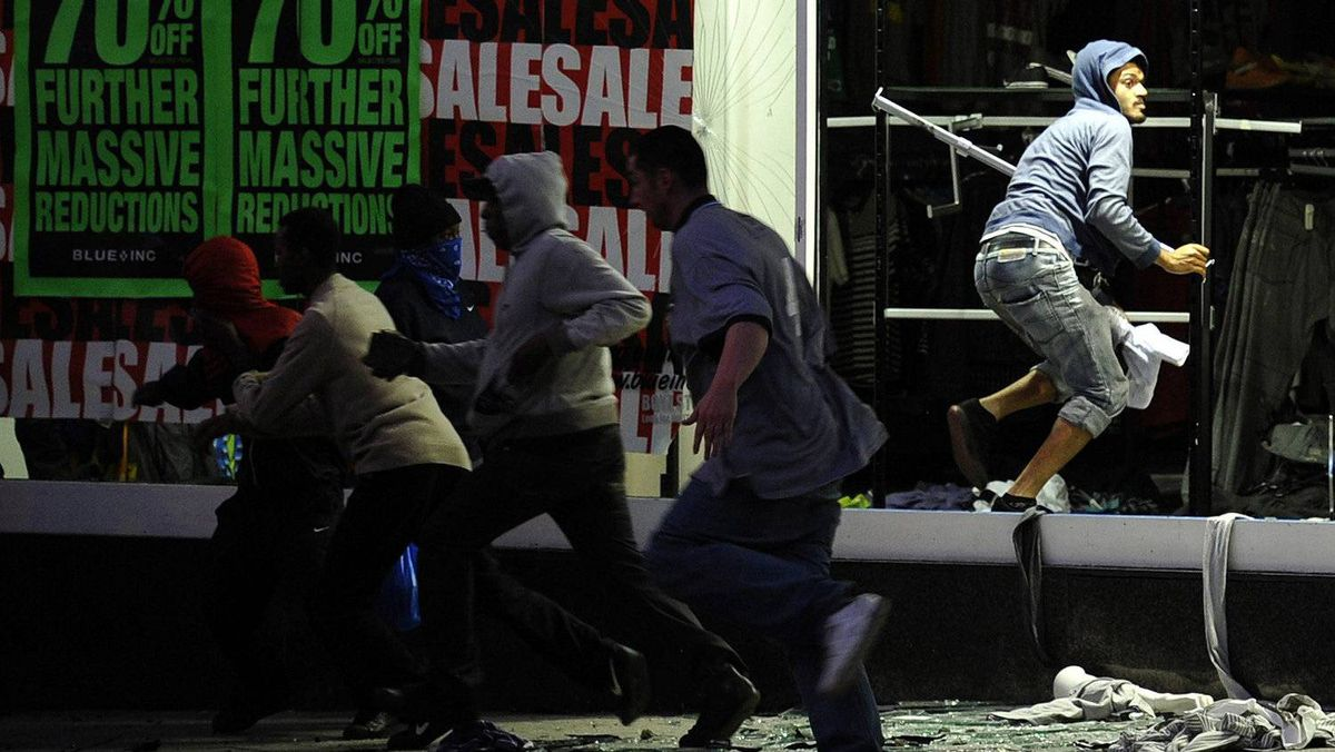 Looters run from a clothing store in Peckham, London August 8, 2011. Youths hurled missiles at police in northeast London on Monday as violence broke out in the British capital for a third night.